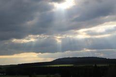 在云彩之间的光束下落 免版税库存照片