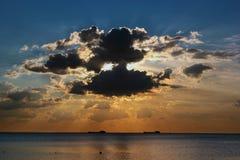 在云彩后的太阳在海 库存照片