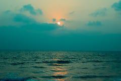在云彩后的日落在海 免版税库存图片