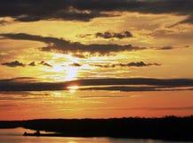 在云彩后的金黄日落 库存图片