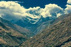 在云彩吞噬的积雪的山上面 库存图片