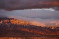在云彩和山的日落 库存图片