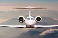 在云彩和阿尔卑斯山的飞机飞行在日落 一个大乘客或货物航空器,企业喷气机的正面图 免版税库存照片