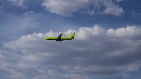 在云彩天空的绿色乘客空中飞机 免版税库存图片