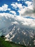 在云彩奇怪形成的山之上 免版税库存照片