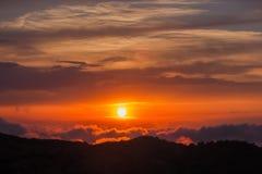 在云彩框架的太阳在日落 库存图片