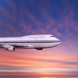 在云彩的乘客飞机在日落或黎明 免版税图库摄影