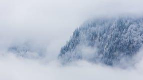 在云彩的冬天山 免版税库存图片