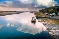 在云彩的反射的渔船在河的由海洋, Aytuy, Chiloe海岛,智利,南美 免版税图库摄影