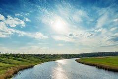 在云彩的太阳在河 库存图片