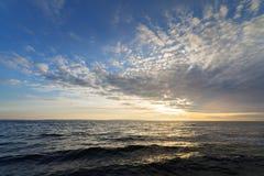 在云彩的太阳在风大浪急的海面 库存照片