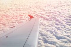 在云彩的平面飞行在黎明 在美好的cloudscape的飞机翼在剧烈的五颜六色的日落或日出期间 旅行和 免版税库存图片