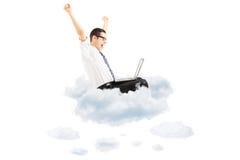 在云彩的愉快的年轻商人飞行与膝上型计算机和gesturi 免版税库存照片