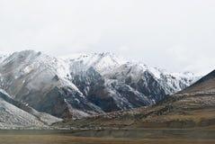 在云彩的斯诺伊山在西藏全景视图 库存照片