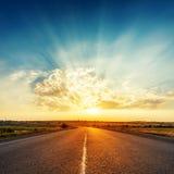 在云彩的日落在向天际的路 免版税库存照片