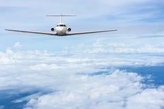 在云彩的班机飞行 免版税库存图片