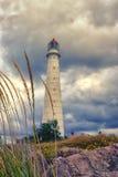 在云彩的老灯塔 免版税库存照片