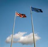 在云彩的英国和欧盟旗子 图库摄影