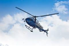 在云彩的直升机飞行 库存照片