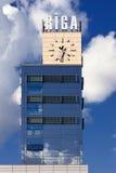 在云彩背景的里加计时火车站  免版税库存照片