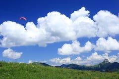在云彩附近的滑翔伞 免版税库存图片