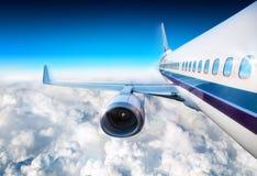 在云彩飞行的飞机 库存图片