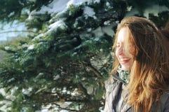 在云杉的分支中的女孩在冬天 免版税库存图片