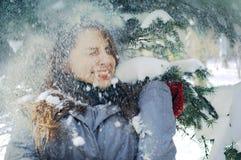 在云杉的分支中的女孩在冬天 库存照片