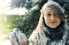 在云杉的分支中的女孩在冬天 免版税库存照片