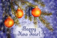 在云杉的分支的橙色圣诞节装饰品在与雪花的蓝色发光的背景 在a的新年快乐上写字 免版税库存照片