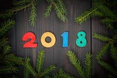 在云杉的树枝中间的装饰木2018个数字在一个黑暗的木板 看板卡圣诞节新年度 库存照片