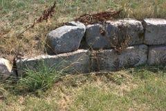 在互相堆积的装饰粗略的不用灰泥只用石块构造的块的部分用生长通过的草创造一面护墙 库存照片