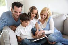 在互联网上连接的愉快的家庭 免版税库存照片