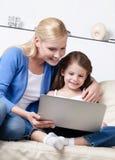 在互联网的小孩儿海浪有她的妈咪的 免版税库存照片