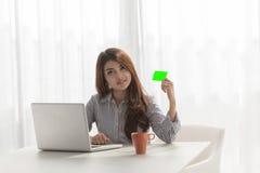 在互联网膝上型计算机的微笑的女实业家购物 库存照片