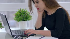 在互联网,少妇上的工作与坐在书桌的膝上型计算机一起使用在轻的办公室 股票视频