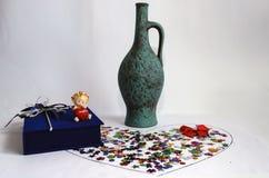 在五彩纸屑和绿色水罐的红色弓 免版税库存照片