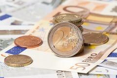 在五枚和五十枚欧元和硬币的有些钞票 免版税库存图片