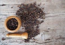 在五谷的黑胡椒与在一张土气桌上的木灰浆 免版税库存图片