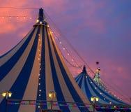 在五颜六色剧烈的日落的天空的马戏场帐篷 免版税库存照片