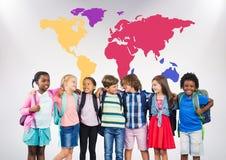 在五颜六色的世界地图前面的多文化学校孩子 免版税库存图片