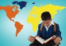 在五颜六色的世界地图前面的男小学生读书 库存图片