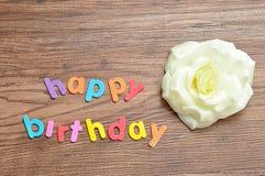 在五颜六色的信件的生日快乐显示与一朵人为白色玫瑰 免版税库存图片