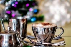 在五颜六色的圣诞节背景的热奶咖啡杯 免版税库存图片