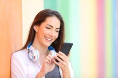 在五颜六色的墙壁上的愉快的女孩检查电话内容的 免版税库存照片