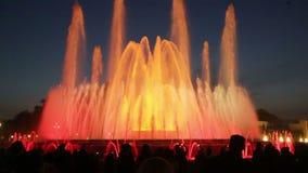 在五颜六色的声音喷泉Montjuic展示的晚上附近观看它的视图和人们在巴塞罗那 股票视频