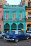 在五颜六色的大厦前面的老蓝色普利茅斯汽车在古巴 免版税图库摄影