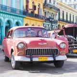 在五颜六色的大厦旁边的老雪佛兰在哈瓦那 免版税库存图片