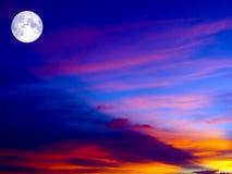 在五颜六色的天空的满月在橙红和深灰云彩 免版税库存图片