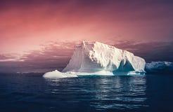 在五颜六色的天空背景的巨大的冰山 免版税库存照片